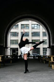 Picture of young woman in heels in a ballet pose, outside under an arch in NYC